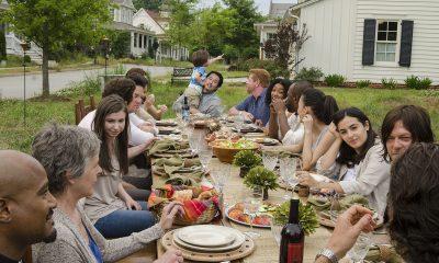 Personagens reunidos em uma mesa cheia de comida em um futuro alternativo de The Walking Dead