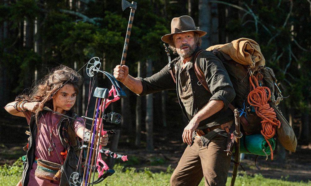 Ariana Greenblatt e Michael Rooker armados em imagem promocional do filme Amor e Monstros