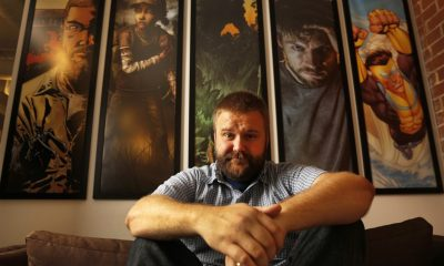 Robert Kirkman sentado em um sofá com alguns quadros de seus projetos ao fundo
