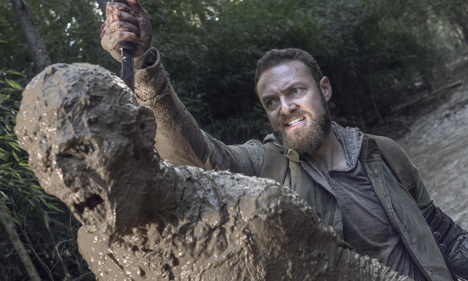 Aaron matando um zumbi sujo de lama em imagem do 19º episódio da 10ª temporada de The Walking Dead