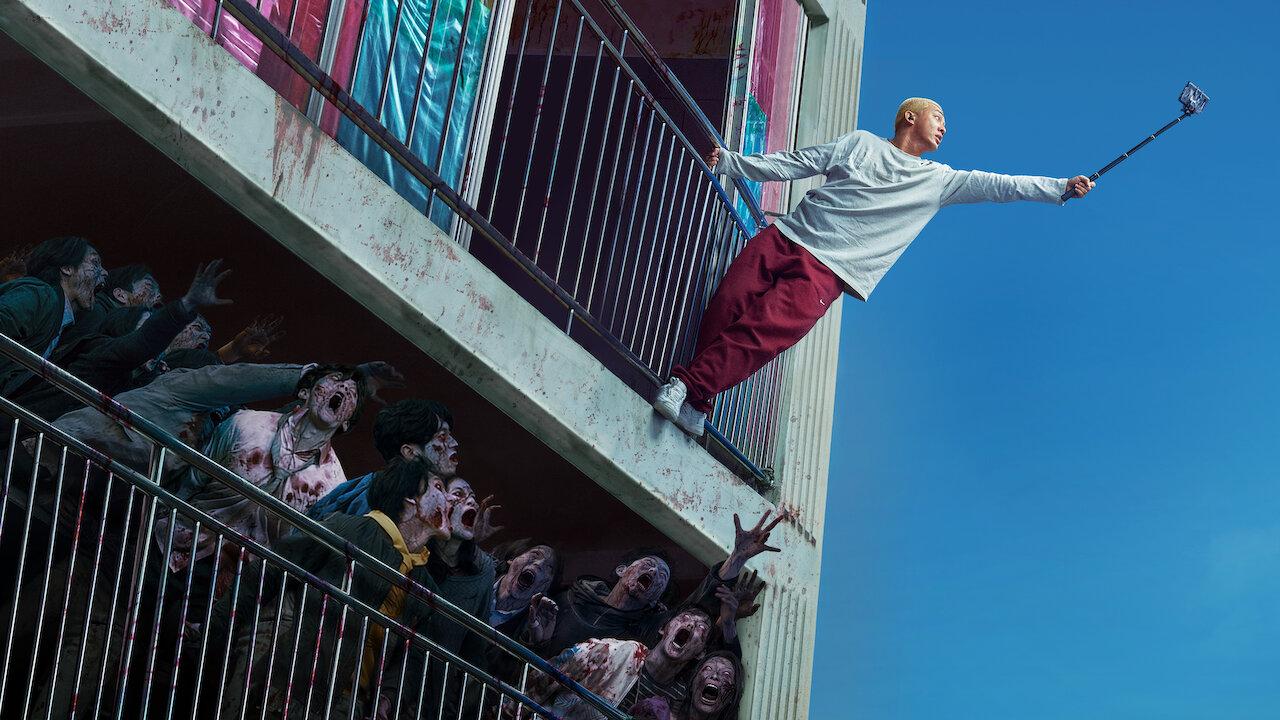 protagonista de #Alive tentando pegar sinal no celular enquanto horda de zumbis tenta devora-lo.