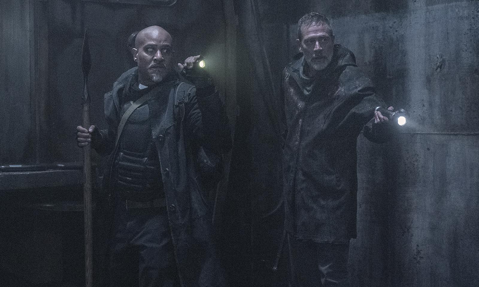 Gabriel e Negan apontando lanternas para algo no metrô do episódio 1 da 11ª e última temporada de The Walking Dead.