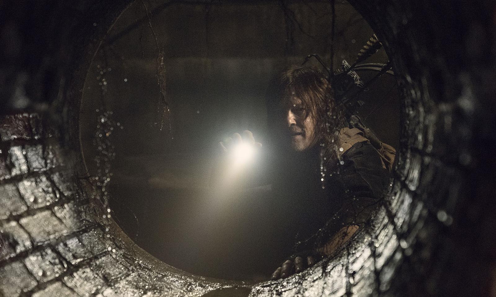 Daryl apontando uma lanterna e observando um túnel no episódio 2 da 11ª temporada de The Walking Dead.