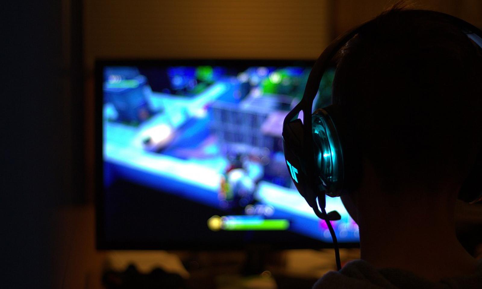 Menino jogando com fone de ouvido e fazendo gameplay.