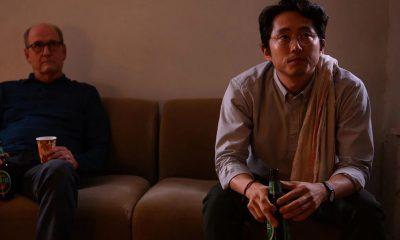 Steven Yeun como Richard sentado no sofá tomando uma cerveja em imagem do filme The Humans.
