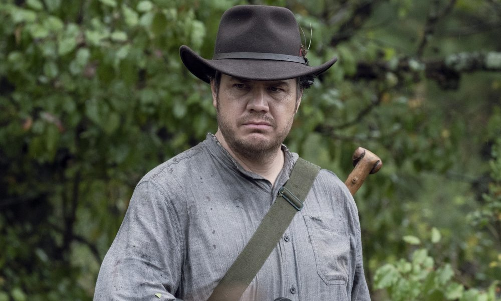 Josh McDermitt como Eugene Porter segurando sua arma em cena da 10ª temporada de The Walking Dead.