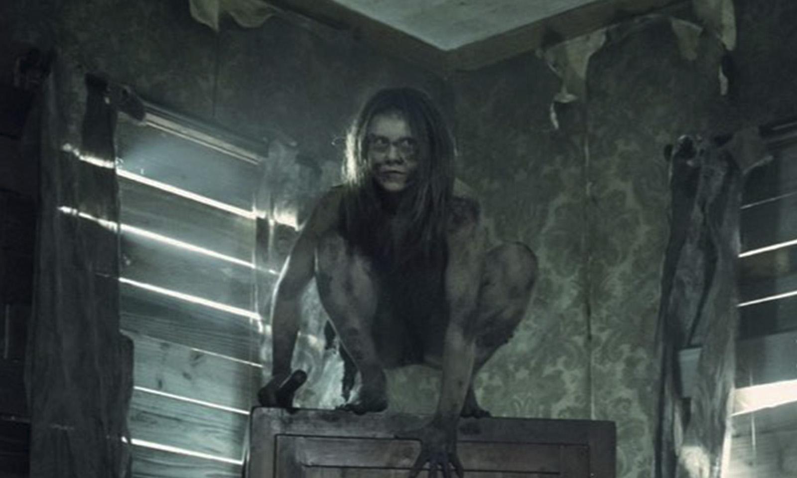 Mulher selvagem segurando algo em cima de alguma coisa em casa abandonada no episódio 6 da 11ª temporada de The Walking Dead.